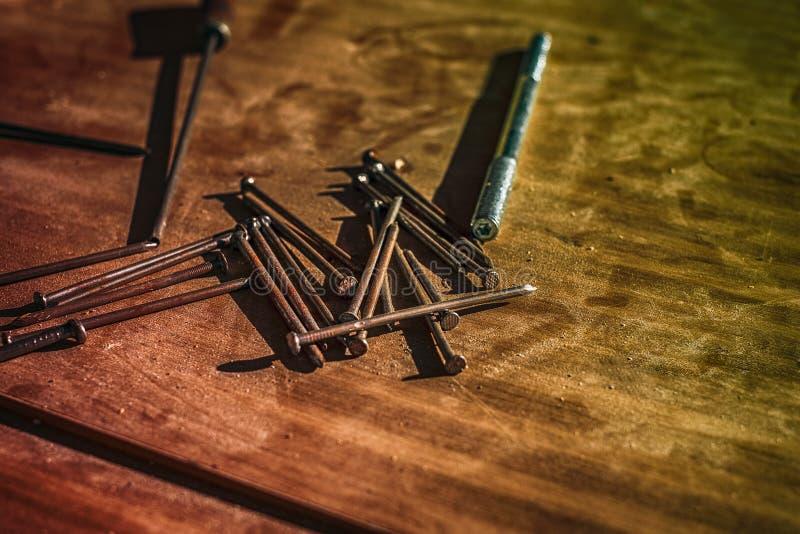 Clous et vis sur la table en bois photographie stock libre de droits