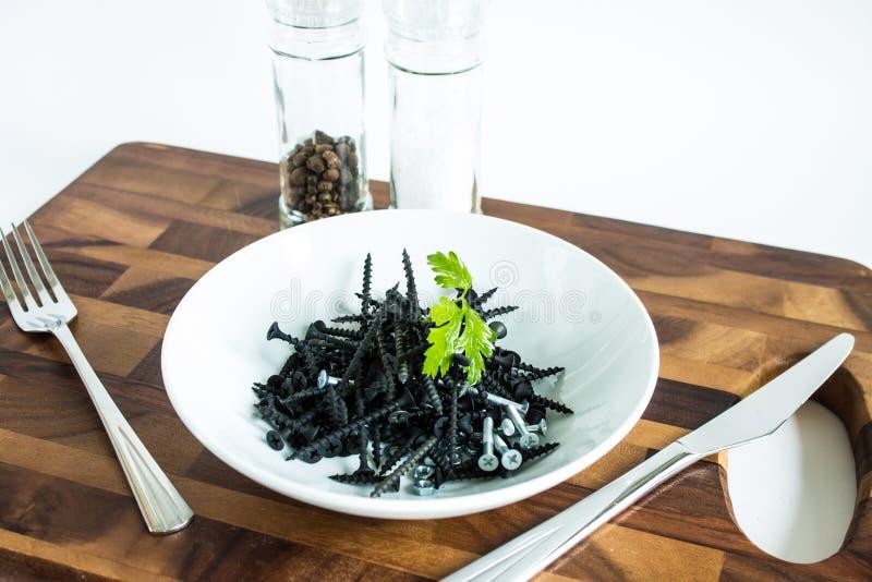 Clous noirs en métal d'un plat blanc photographie stock