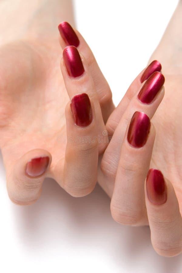 Clous rouges de femme sur les deux mains photo stock