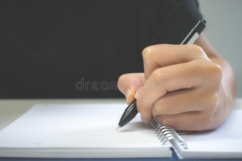 Clouse para arriba Una pluma de la mano que escribe en el cuaderno fotografía de archivo