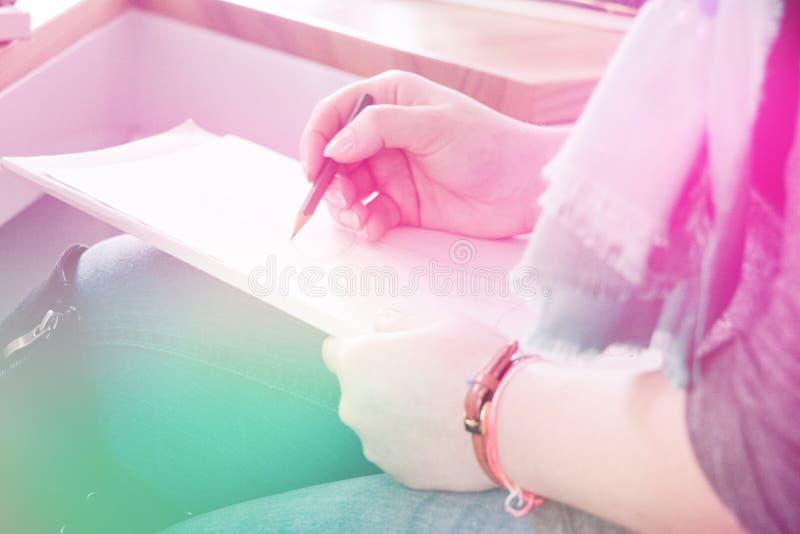 Clouse-up女性手写在笔记本的,轻定调子 库存照片