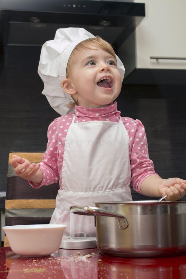 Clouse-up portreta uśmiechu mała śliczna dziewczyna w szefa kuchni kostiumu Matka pomagier 2 roczniak zdjęcia royalty free