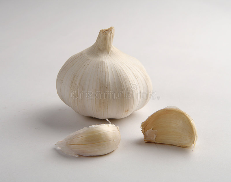 Clove of garlic. And two pieces more on white background royalty free stock photography