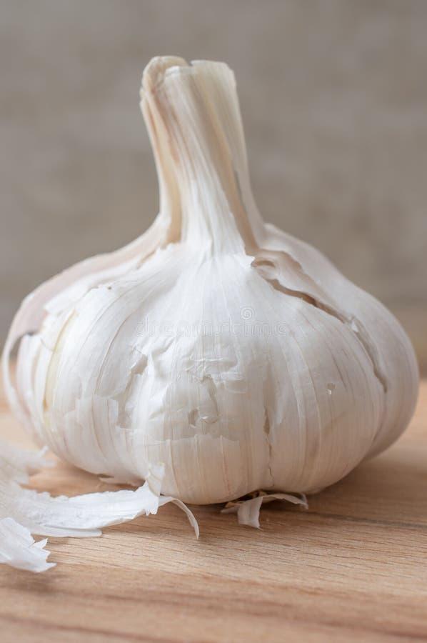 Clove garlic vertically. Clove garlic close up vertically on a wooden board royalty free stock photography