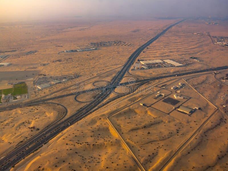 Cloverleaf highway in the desert. Flight over Dubai cloverleaf highway surrounded by sand stock images