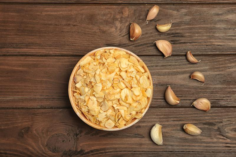 Cloves and bowl with dried garlic flakes on wooden background royalty free stock image