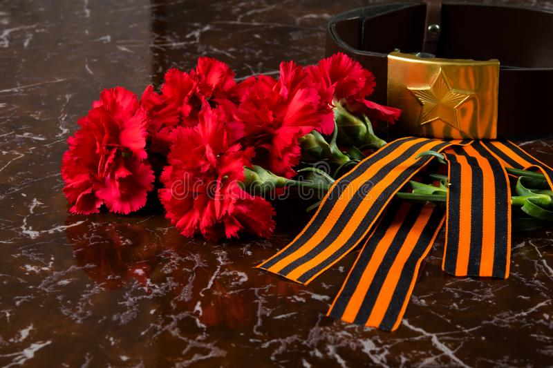 Cloves, a military belt and a St. George ribbon on the background of the monument stock photo