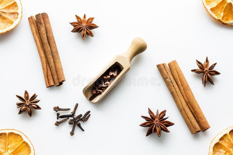 Cloves na drewnianej miarce z cynamonowymi kijami, gwiazdowym anyżem i pomarańcze plasterkami, zdjęcie royalty free