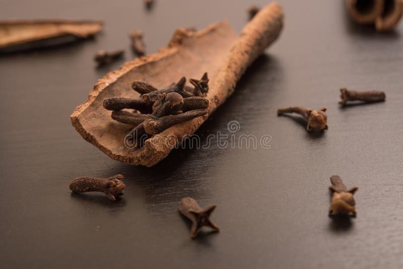 Cloves randomly arranged in Cinnamon. In a black background stock images