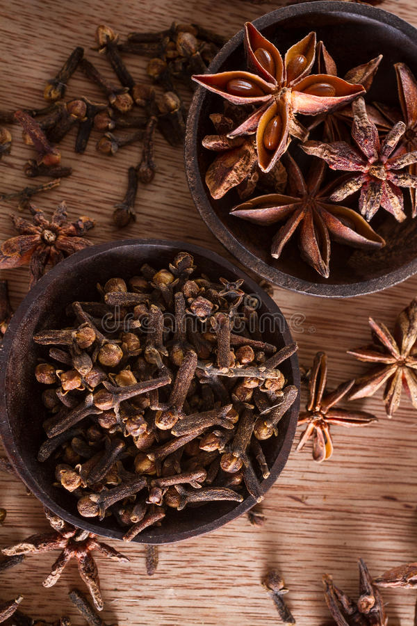 Cloves and star anise. Assorted spices for food and decoration: star anise and cloves, against a wodden background royalty free stock images