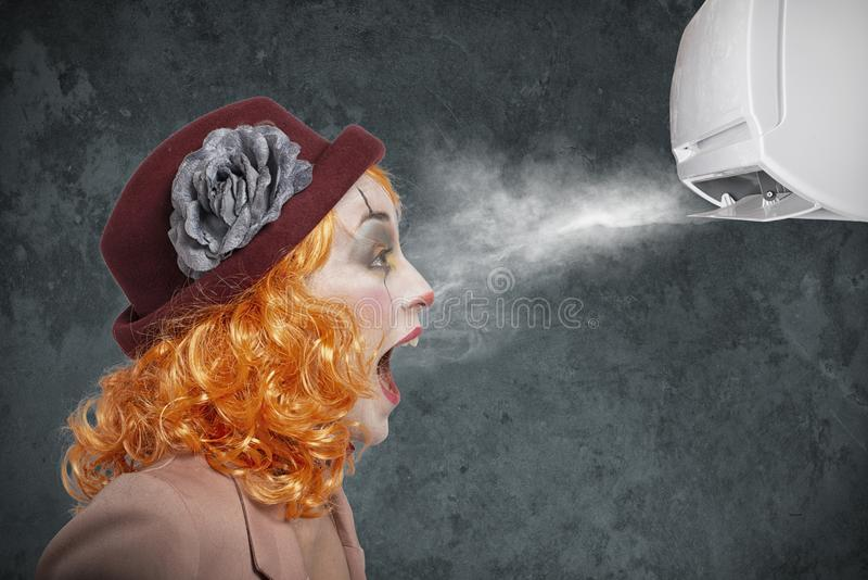 Clown amazed by the fresh of air conditioner royalty free stock image