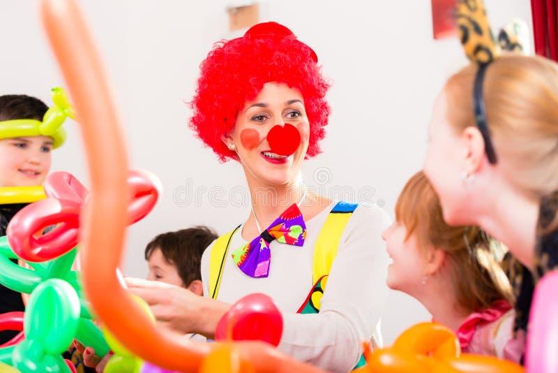 Clown bij de partij van de kinderenverjaardag met jonge geitjes stock afbeelding