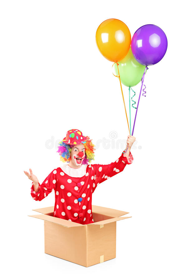 Download A Clown In A Cardboard Box Holding Balloons Stock Image - Image: 30247215