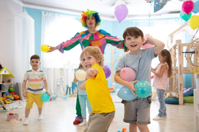Clown at children birthday party entertaining kids. Children play with ballons. Clown at children birthday party entertaining group of kids. Children play with royalty free stock images