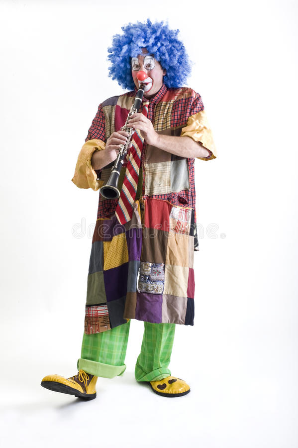 Clown and clarinet. Clown playing the clarinet isolated on white stock images