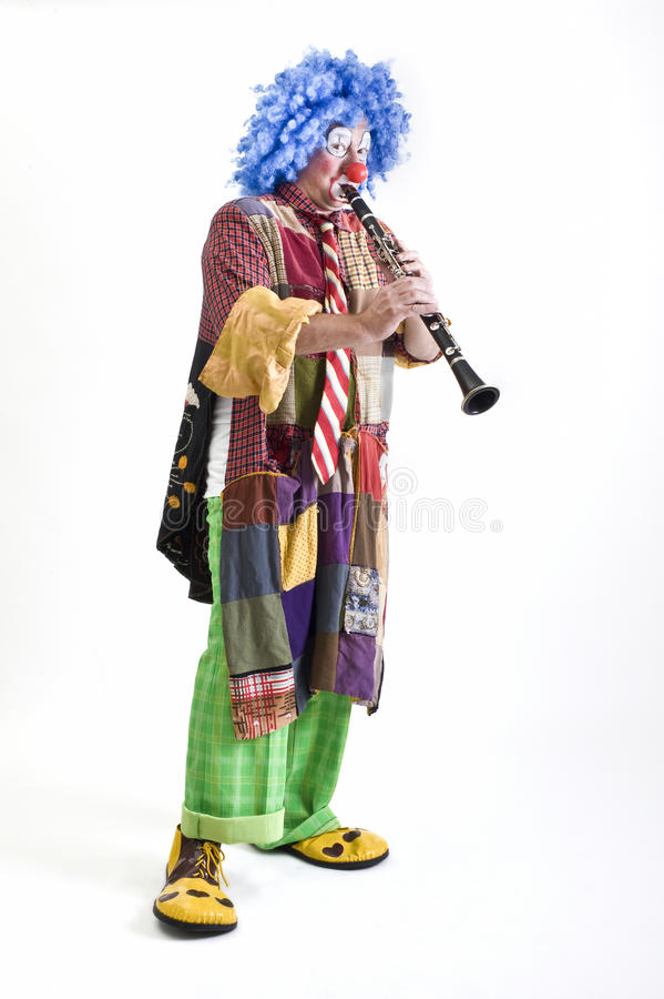 Clown and clarinet. Clown playing the clarinet isolated on white stock photo