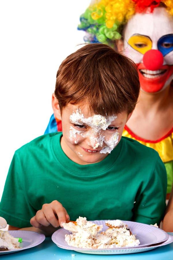Clown d'enfant d'anniversaire mangeant le gâteau avec le garçon ensemble Gosse avec le visage malpropre images stock