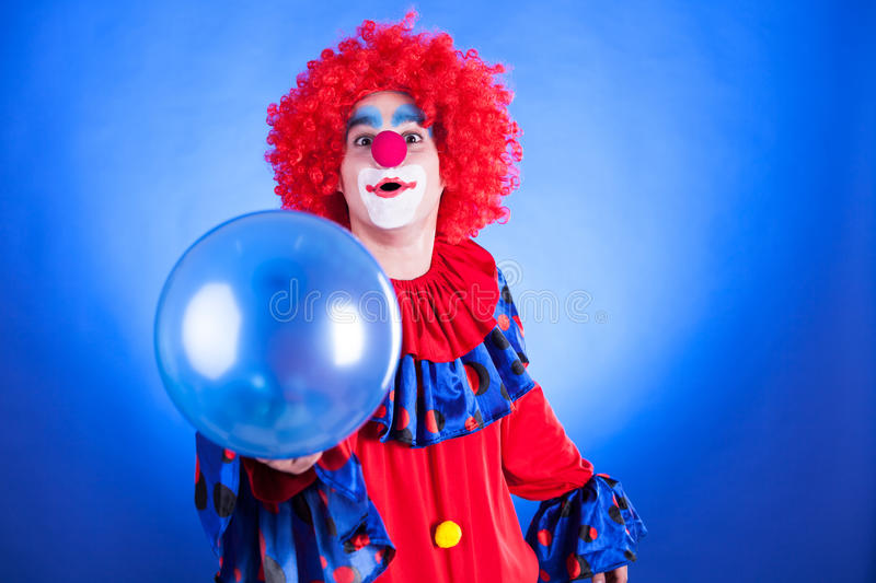 Clown de sourire dans le studio avec le ballon photo stock