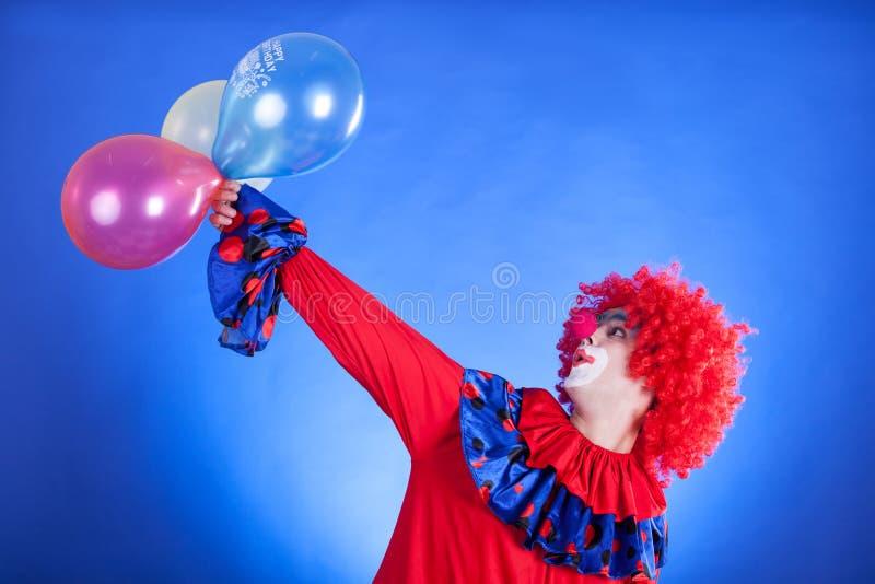 Clown de sourire dans le studio avec le ballon photographie stock libre de droits