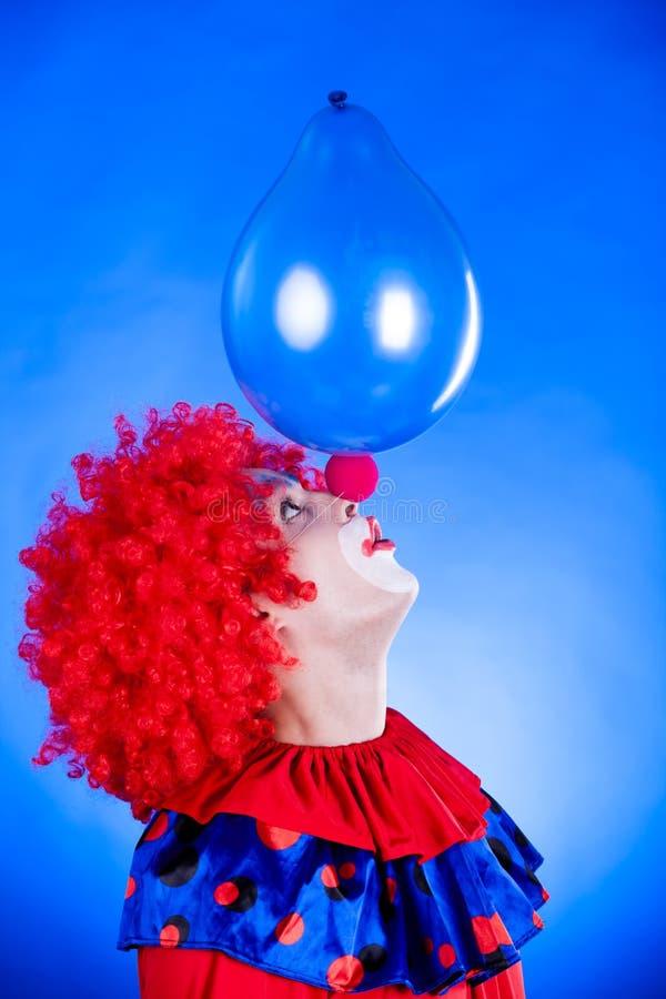 Clown de sourire dans le studio avec le ballon image stock