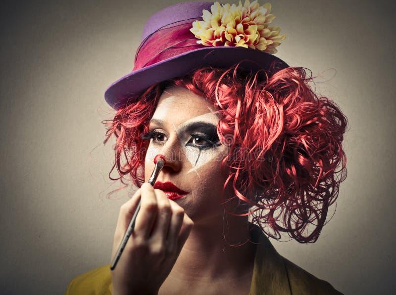 Clown, der auf etwas Make-up sich setzt stockbild