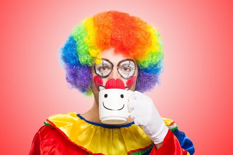Clown, der von einer Schale trinkt lizenzfreie stockfotografie