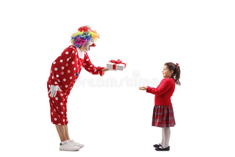 Clown die een heden overhandigen aan een klein meisje royalty-vrije stock foto