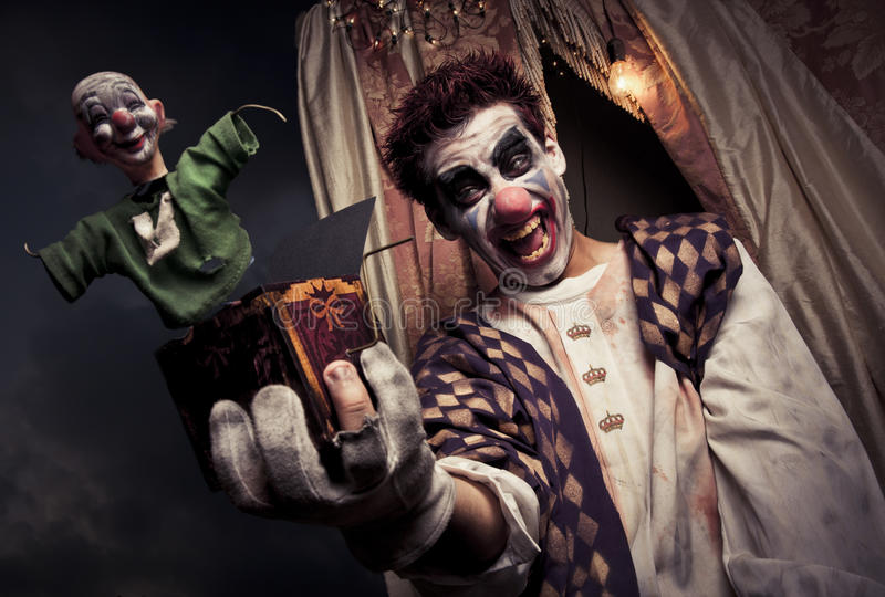 Clown effrayant retenant un jouet de Jack-in-the-box photo stock