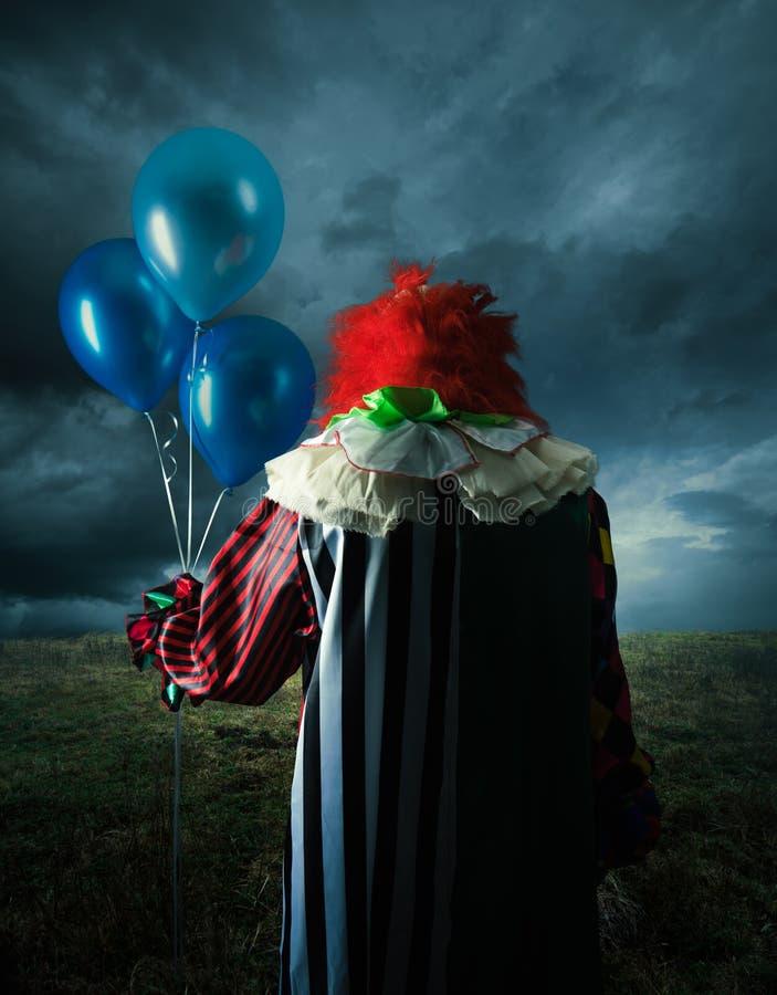 Clown effrayant sur un champ la nuit photos stock