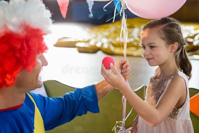 Clown en meisje die met elkaar tijdens verjaardagspartij interactie aangaan stock afbeeldingen