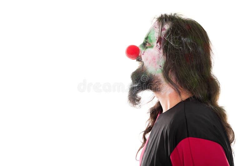 Clown ensanglanté dans un profil de visage regardant un copyspace, d'isolement photographie stock libre de droits
