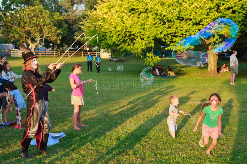 A clown entertaining children with giant soap bubbles. A man with face paint and a large bubble maker, creating huge bubbles for kids to chase after royalty free stock images