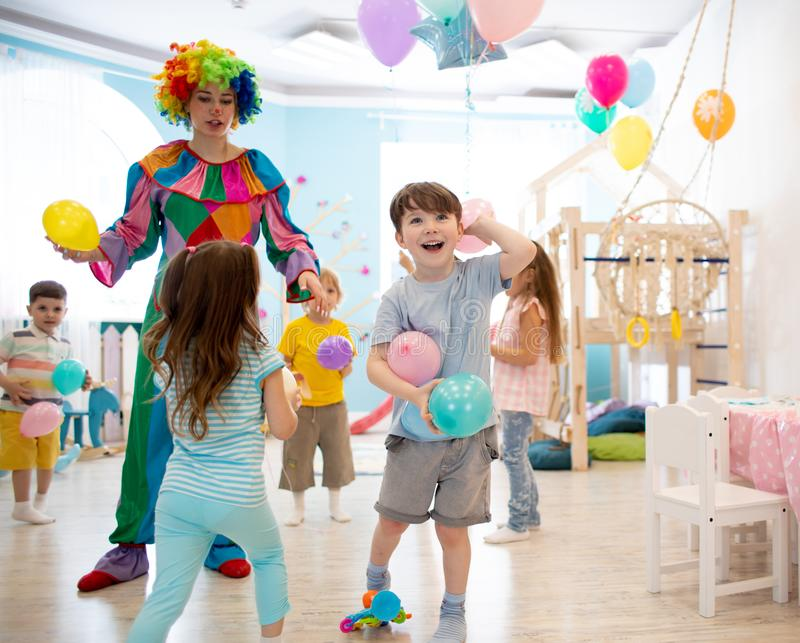 Clown entertains children at birthday party. Kids play with colorful ballons royalty free stock photos
