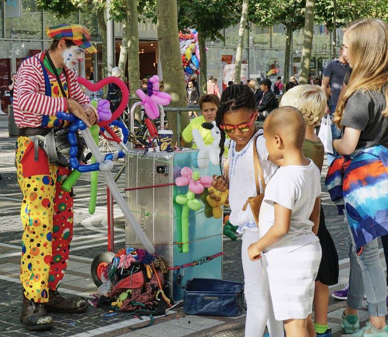 Clown Entertains Kids op de straat in Frankfurt, Duitsland stock afbeelding