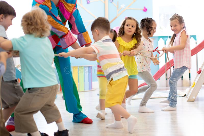 Clown entertains children at birthday party. Kids teams compete joyfully pulling rope. Clown entertains preschool children at birthday party. Kids teams compete stock image