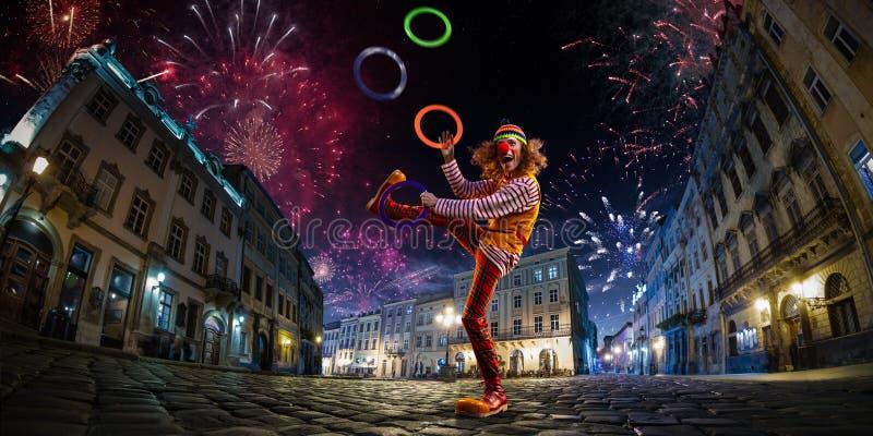 Clown för whit för kapacitet för nattgatacirkus, jonglör Festivalstadsbakgrund fyrverkerier och berömatmosfär Bred engle fotografering för bildbyråer