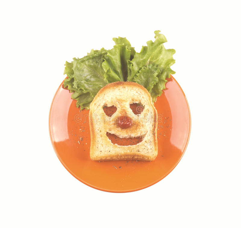 Clown face of a slice of bread, lettuce hair, red nose. Clown face of a slice of bread, lettuce hair, red nose stock photography