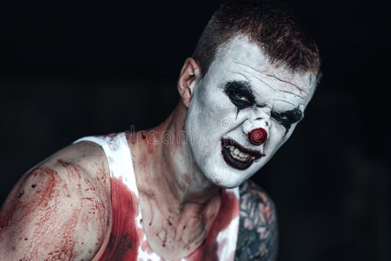 Clown-fou ensanglanté avec la hache photographie stock libre de droits