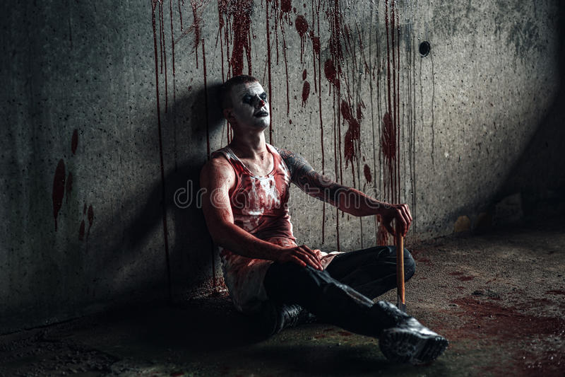 Clown-fou ensanglanté avec la hache photo stock