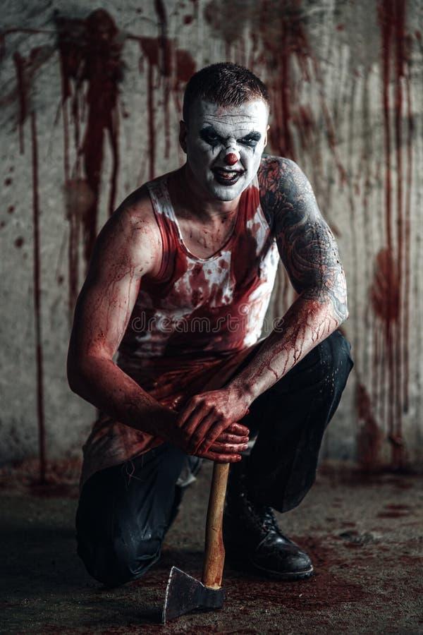 Clown-fou ensanglanté avec la hache photos stock