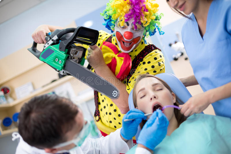 Clown from horror with chainsaw in dental clinic. Crazy clown from horror threatens girl with chainsaw in dental clinic stock images