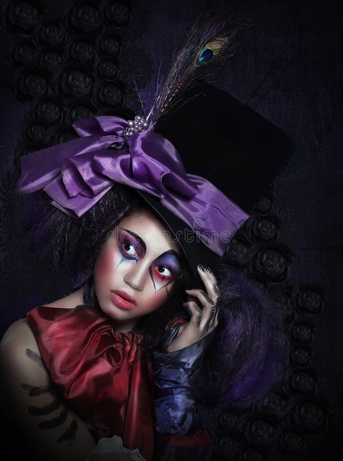 Clown i utsmyckad karnevalhatt med konstnärlig makeup fotografering för bildbyråer