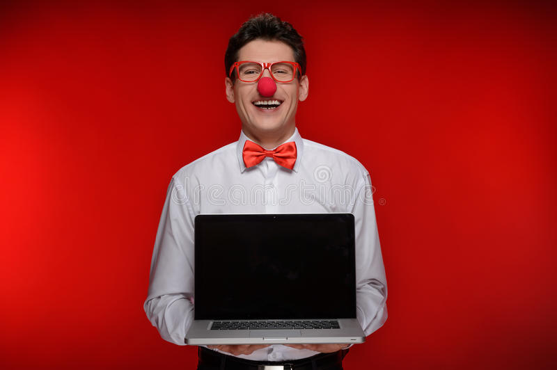 Clown with laptop. Cheerful man with clown holding a laptop while standing isolated on red stock photography