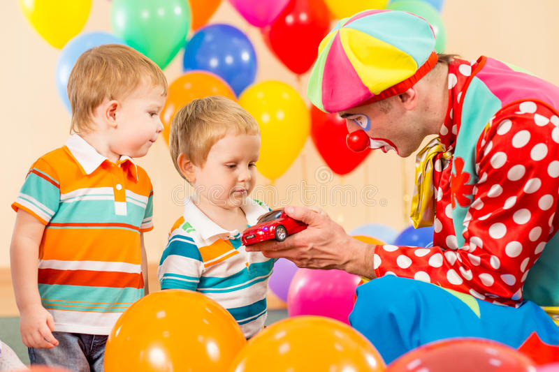 Clown making present kid boy on birthday party stock images