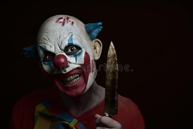 Clown mauvais effrayant avec un couteau image libre de droits