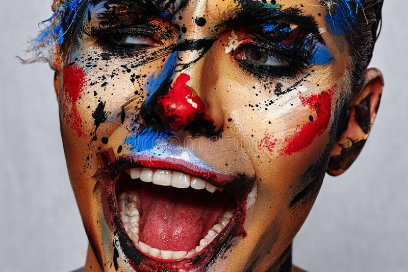 Clown mauvais riant aliéné avec l'art créatif de visage photos stock