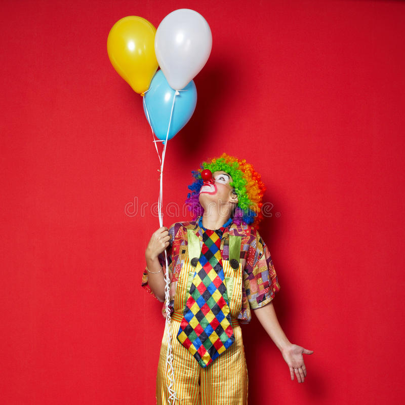 Clown med ballonger på röd bakgrund fotografering för bildbyråer