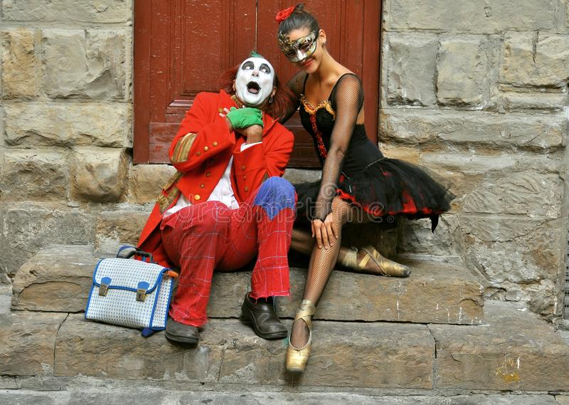 When the clown met the ballerina. Street artist in Florence , Italy.Funny , happy clown male with a very Young and beautiful dancer on stairs in front of an old stock photos