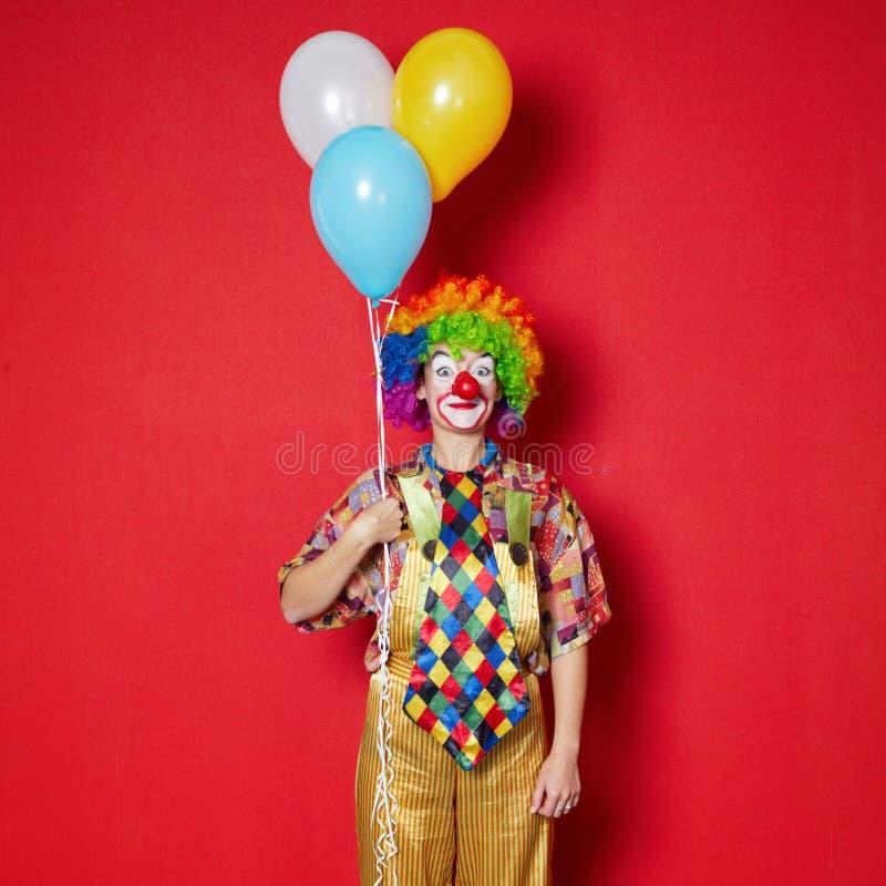 Clown met ballons op rode achtergrond stock afbeelding