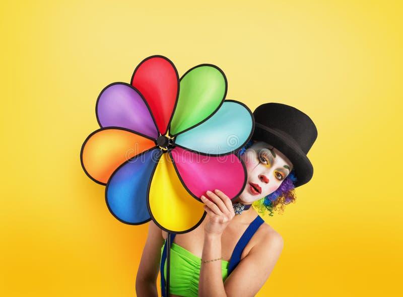 Clown met gekleurde schroef op gele achtergrond royalty-vrije stock afbeelding